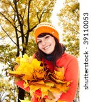 Girl in autumn orange hat with leaf group near tree.  Outdoor. - stock photo