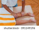 massage therapist massaging legs | Shutterstock . vector #391149196