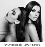 fashion black and white photo of two beautiful girls with dark hair and evening makeup, posing in studio