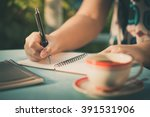 woman hand writing journal on... | Shutterstock . vector #391531906