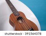wooden ukulele lying on a white ... | Shutterstock . vector #391564378