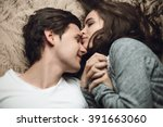 Stock photo beautiful brunette girl and guy lying in bed and holding tightly hands the concept of tenderness 391663060