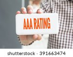 Small photo of Man hand showing AAA RATING word phone with blur business man wearing plaid shirt.