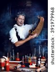 Small photo of Crazy medieval scientist working in his laboratory with old manuscripts. Alchemist. Halloween.