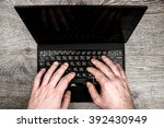 black laptop on wood with hands ... | Shutterstock . vector #392430949