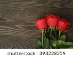 Three Red Roses On Wood Table ...