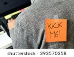 closeup of a young man with a paper with the text kick me attached to his back