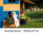 little cute curios girl looking into the blue window of wooden playhouse in the countryside garden with blooming flowers