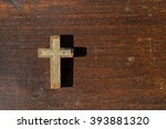 a small wooden cross with gold... | Shutterstock . vector #393881320