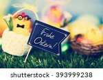 Small photo of a funny teddy chick, emerging from a dot-patterned eggshell, with a black flag-shaped signboard with the text text Frohe Ostern, happy Easter in German, and some decorated eggs on the grass