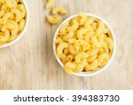 Small photo of raw macaroni in bowl on wooden background.