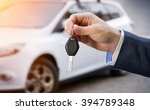 male holding car keys with car...