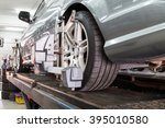 Small photo of Closeup of tire clamped with aligner undergoing auto wheel alignment in garage