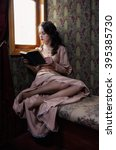 Young woman in beige vintage dress of early 20th century reading book in coupe of retro railway train