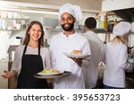 Small photo of Happy chefs and young nippy in apron working at restaurant kitchen