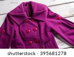 Small photo of Woman's fashionable purple coat. Purple coat on wooden background. Colorful coat from new collection. Bright stylish coat for spring.