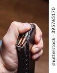 Small photo of Loading 5.56 ammo magazine for machine guns in hand