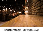 Stock photo empty wood table top of bar with blur of cafe restaurant in dark night background selective focus 396088660