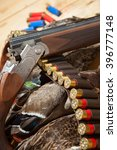 Small photo of Gun, hunting, a dead duck, and ammunition on the table