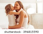 Small photo of Sweet little girl is hugging and kissing her beautiful young mom in cheek while sitting on bed at home