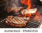 steaks cooking over flaming... | Shutterstock . vector #396861016