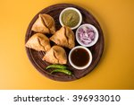 Small photo of Veg Samosa - is a crispy and spicy Indian triangle shape snack which has crisp outer layer of maida & filling of mashed potato, peas and spices. Served with fried green chilly, onion & chutney/ketchup