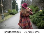 A Woman In A Burgundy Hat And...