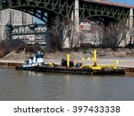 A small tugboat attached to a barge is moored to the bank of the Cuyahoga River in Cleveland, Ohio - stock photo