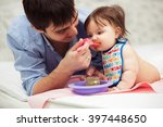 father feeding baby girl on... | Shutterstock . vector #397448650