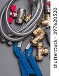 Small photo of Adjustable spanner with assorted plumbing fittings and hose on grey surface