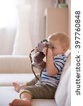 Small photo of Cute adorable toddler boy sitting on the sofa in the living room and playing with vintage photo camera. Child taking picture with old camera. Future photographer. Kid with retro camera.