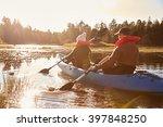 Couple Kayaking On Lake  Back...