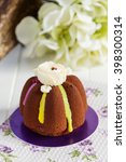 Small photo of Mini mousse cakes covered with chocolate velour and decorated with colorful glaze with cream flowers. Modern european cake on floral background. Shallow focus