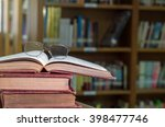 glasses on the books in library ... | Shutterstock . vector #398477746