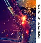 Small photo of Metal Cutting With Acetylene Gas. Workman is working by use torch cut the iron in factory. Spark splash around the ground.
