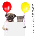 Stock photo cat and dog holding balloons peeking from behind empty board isolated on white background 399216193