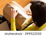 woman opening cardboard box  | Shutterstock . vector #399522520