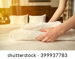 Stock photo close up of hands putting stack of fresh white bath towels on the bed sheet room service maid 399937783