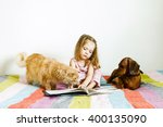 Stock photo little girl reading a book pet on the bed with multicolored bedspread next maine coon cat and 400135090
