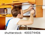Stock photo handyman fixing kitchen s cabinet with screwdriver 400374406