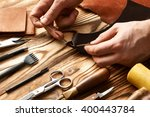 man working with leather using... | Shutterstock . vector #400443784