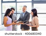 Small photo of Real estate agent handing over agreement paper to couple for their signature