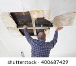 man repairing collapsed ceiling.... | Shutterstock . vector #400687429