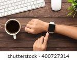 Hand Using Smartwatch On Desk...