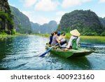 Tourists traveling in boat along the Ngo Dong River and taking picture of the Tam Coc, Ninh Binh, Vietnam. Rower using her feet to propel oars. Landscape formed by karst towers and rice fields.