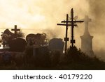 All Saints, cemetery at sunset with cross and silhouetted against sky, - stock photo