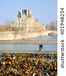 Small photo of PARIS, FRANCE - MARCH 12, 2016: Love locks bridge in Paris and the view of the Louvre museum. Ritual of affixing padlocks, as symbol of love, is spread from 2000s.