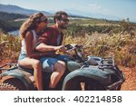 Small photo of Man and woman having fun on an off road adventure. Couple riding on a quad bike in countryside on a summer day.