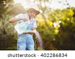Smiling Woman Watering Plants...