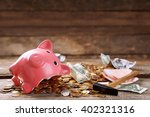 Broken Piggy Bank With Cash An...